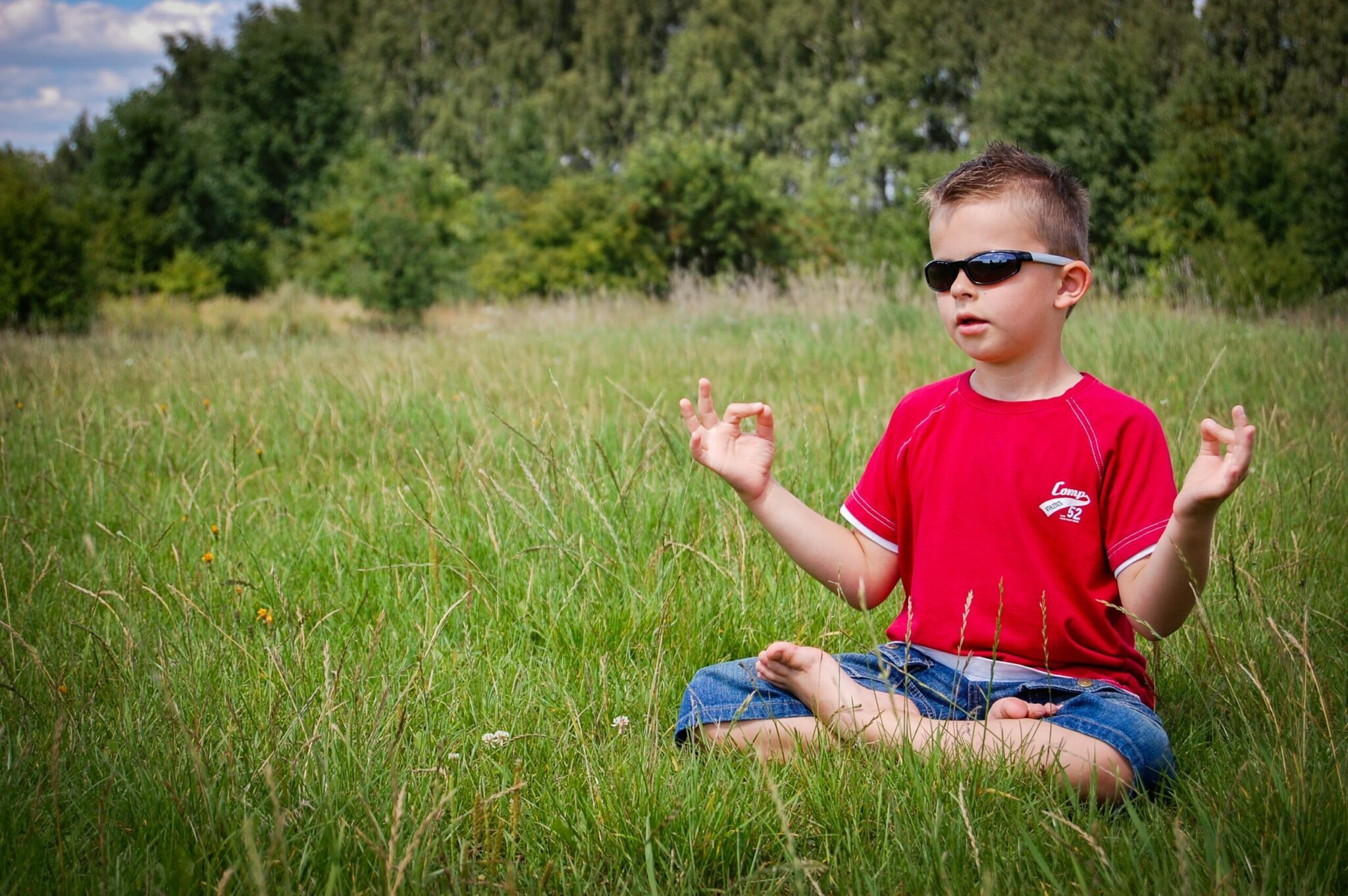 Small boy in sunglasses meditating